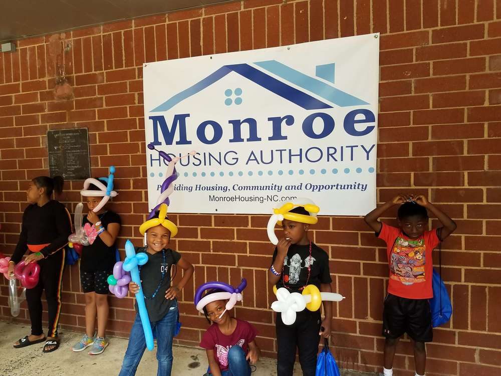 kids with balloon toys in front of Monroe housing authority sign